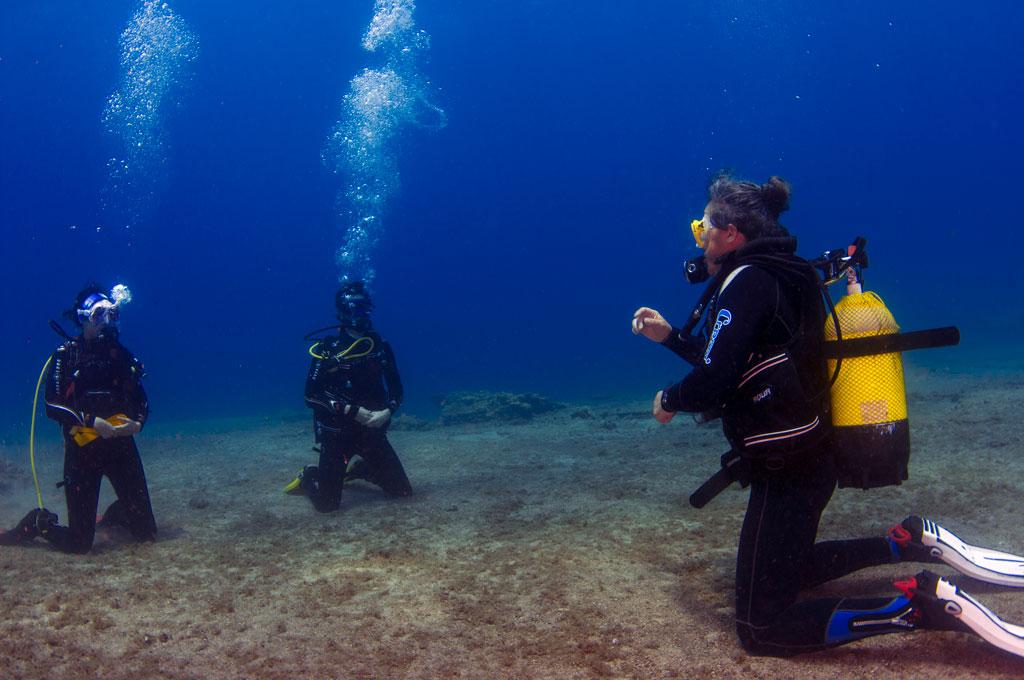 Instructor y dos alumnos de rodillas en el fondo en un curso de buceo en Tenerife Sur Las Galletas
